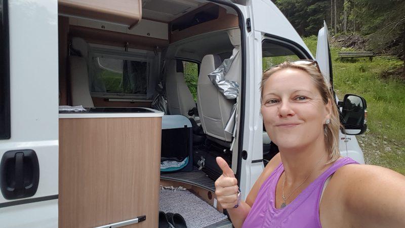 Zwei Frauen sitzen auf Campingplatz lachend mit einem